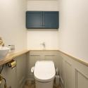 框デザインの腰壁や収納扉、ヘリボーン柄の床がレトロ感を出しているトイレ