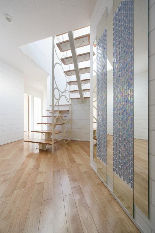 スタイリッシュな階段にガラスモザイクと鏡でオシャレに演出された壁がお出迎えしてくれる玄関ホール