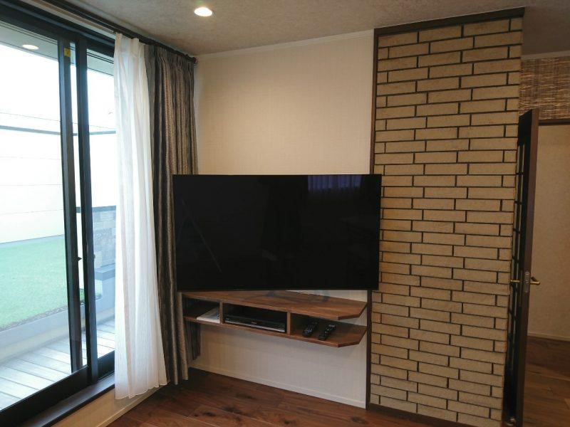テレビは壁掛けで設置、テレビ周りに必要な機器は造作棚に収納。テレビ横には壁紙を変えてお部屋のアクセントにしました。